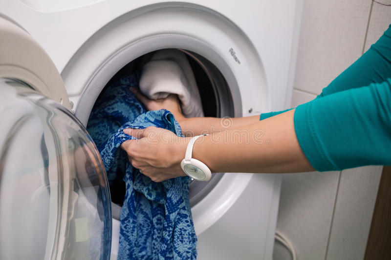 Putting a cloth into washing machine royalty free stock photography
