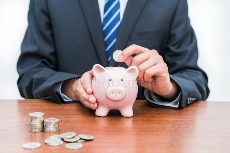 Putting coins into piggy Bank-The concept of savings stock photo