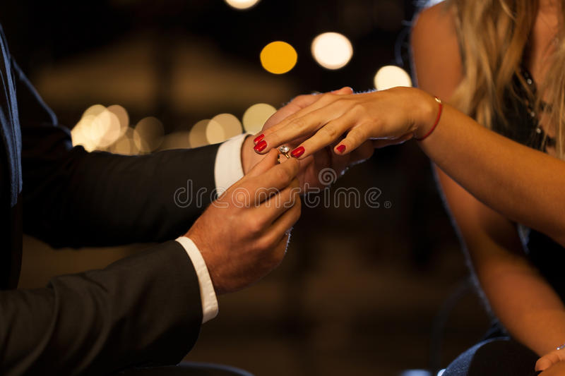 Putting on an engagement ring stock images