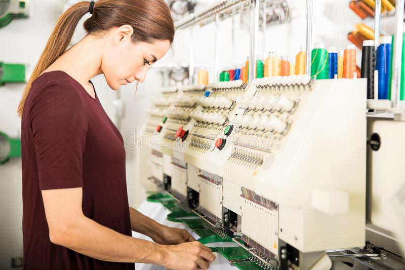 Putting garments in place for embroidery. Profile view of a woman putting many garments in place in an embroidery machine at a factory royalty free stock photos