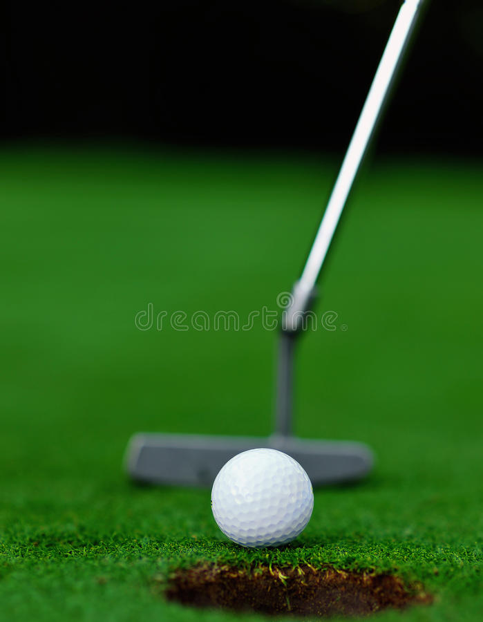 Putting on the green. Putting a golf ball on the green of a golf course stock image