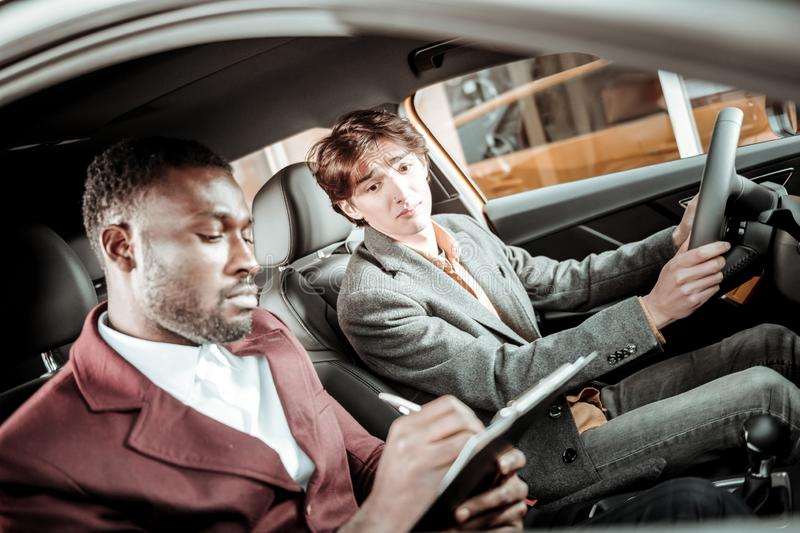 Driving instructor putting marks after driving to young student. Putting marks. Professional driving instructor putting marks after driving to young student royalty free stock images