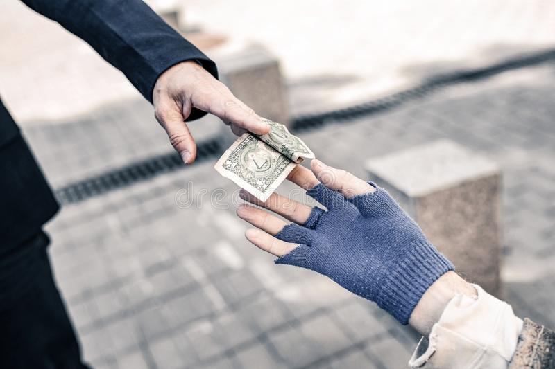 Pedestrian in dark costume carrying money bill and gifting it royalty free stock photography