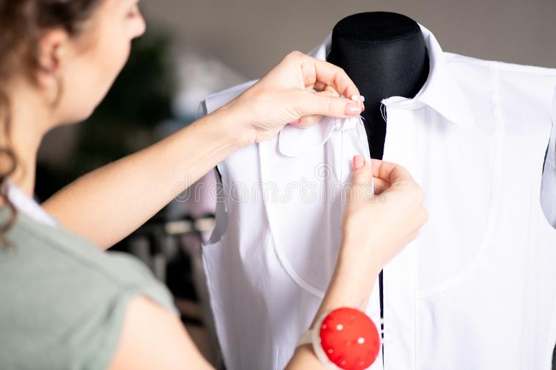 Putting pins. Young professional seamstress pinning up front detail of white cotton blouse while working over new order royalty free stock photo
