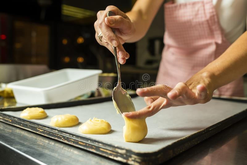 Putting a puff pastry on a cake baking tray stock images