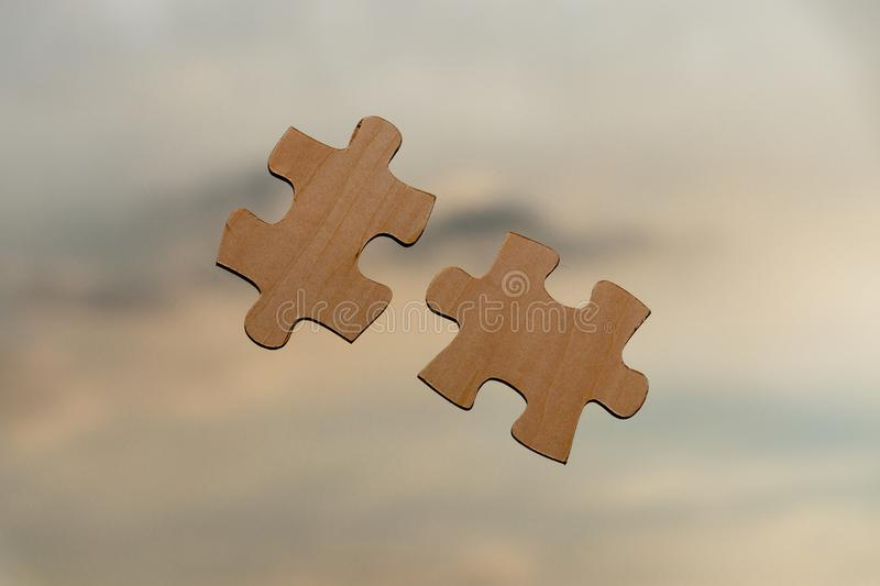 Putting puzzle pieces together on sky background with clouds stock photos