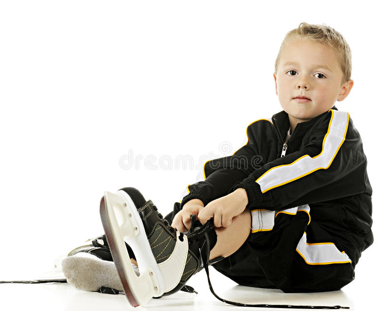 Putting on the Skates. A handsome preschooler in his hockey uniform putting on his skates. On a white background. On a white background stock photos