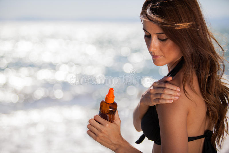 Putting on some tanning lotion. Gorgeous young woman rubbing some tanning lotion on her shoulder at the beach royalty free stock photos