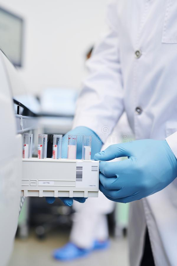 Putting test tube section into modern medical machine stock image