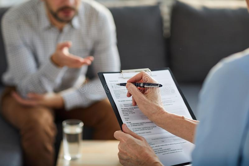 Putting tick in document. Hand of mature professional counselor with pen over medical document putting tick during conversation with patient royalty free stock photo