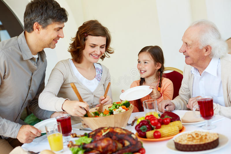 Putting vegs on plates. Woman putting cooked vegs on plate of little girl stock image