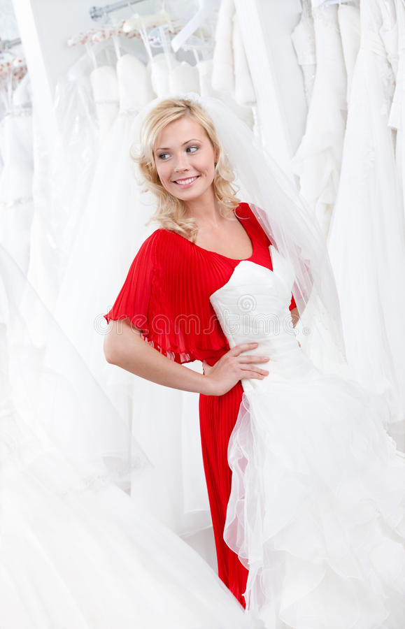 Putting A Wedding Gown On Stock Image