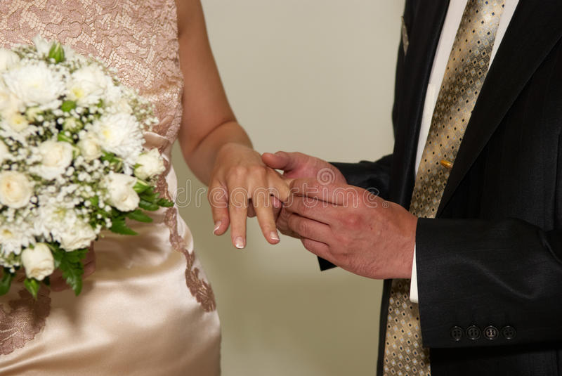 Putting on a wedding ring. Man holding woman's hand and putting wedding ring on the finger royalty free stock photo