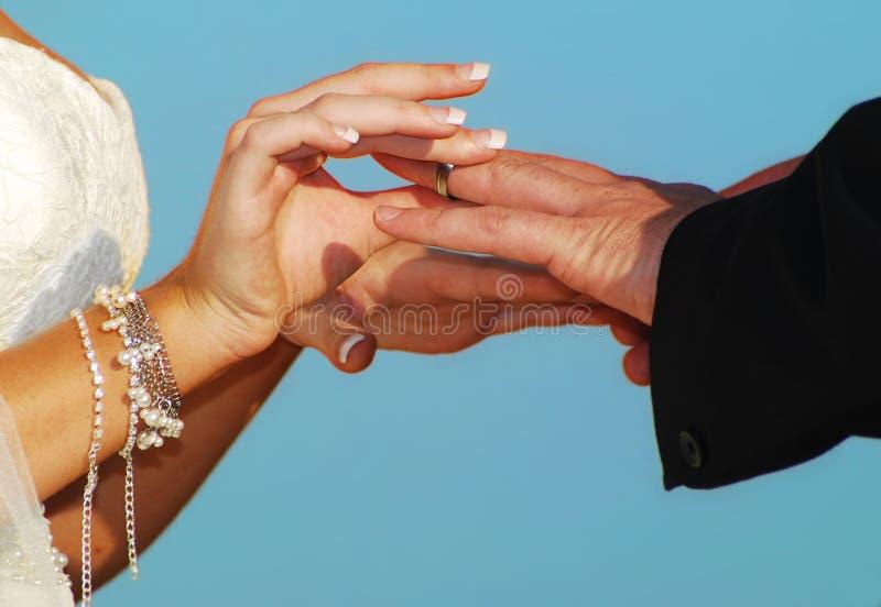 Putting on wedding ring royalty free stock photo