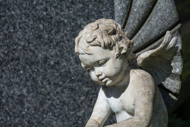 Putto或儿童天使雕象作为一块严重石头在公墓 库存照片