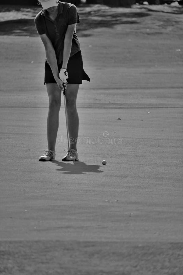 Putts femeninos del golfista en blanco y negro fotografía de archivo libre de regalías