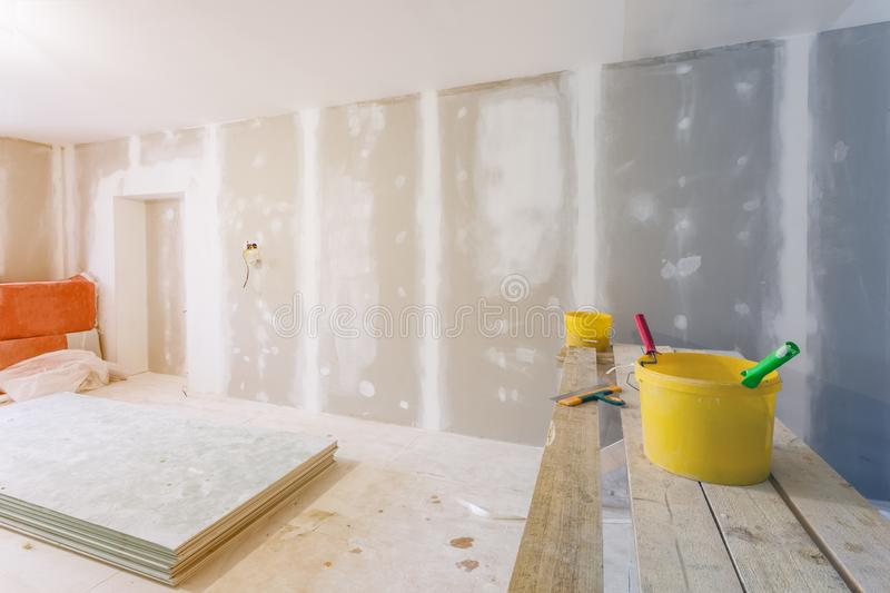 Putty knife, yellow buckets with glue and glue rollers on the wooden board in room is under construction stock photography