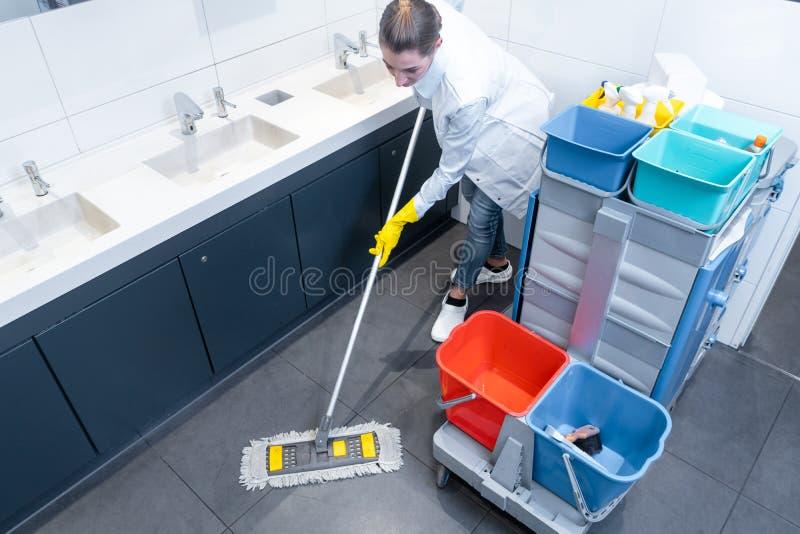 Putzfrau, die den Boden in der Toilette wischt lizenzfreie stockfotografie
