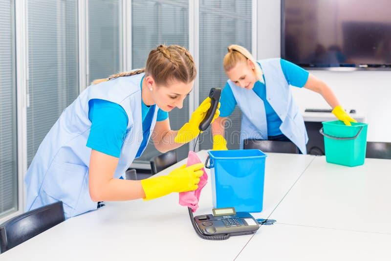 Putzfrauen, die im Büro arbeiten lizenzfreie stockfotos