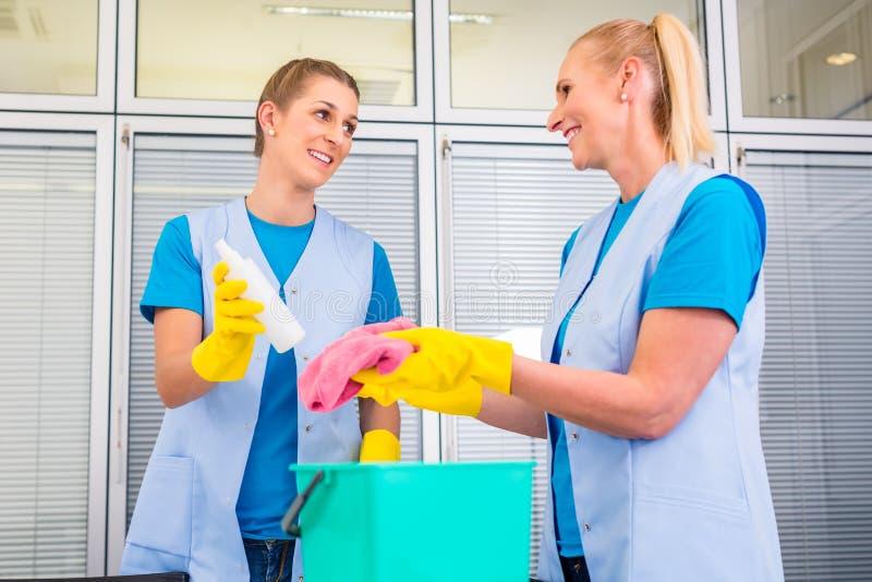 Putzfrauen, die im Büro arbeiten stockfotografie
