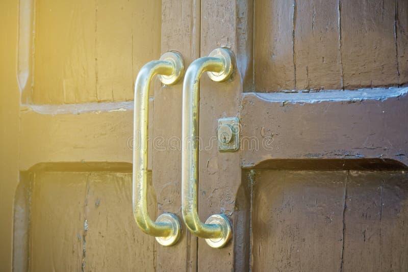 Puxador da porta antigo na porta de entrada de madeira velha imagem de stock