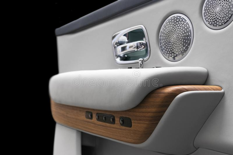 Puxador da porta com os botões do controle da janela de poder de um automóvel de passageiros luxuoso O branco perfurou o interior imagem de stock royalty free