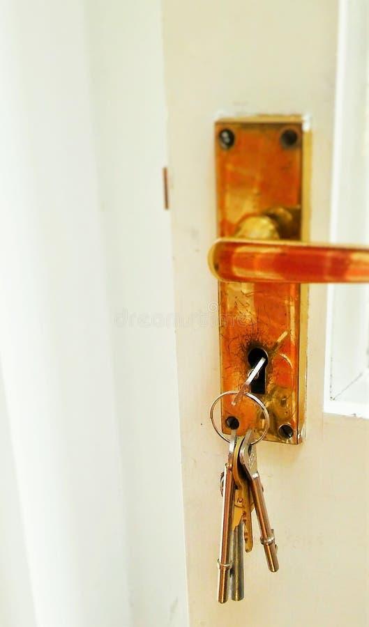 Puxador da porta de bronze com chaves no fechamento fotografia de stock