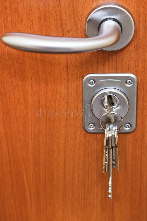 Puxador da porta e grupo de chaves no buraco da fechadura imagens de stock