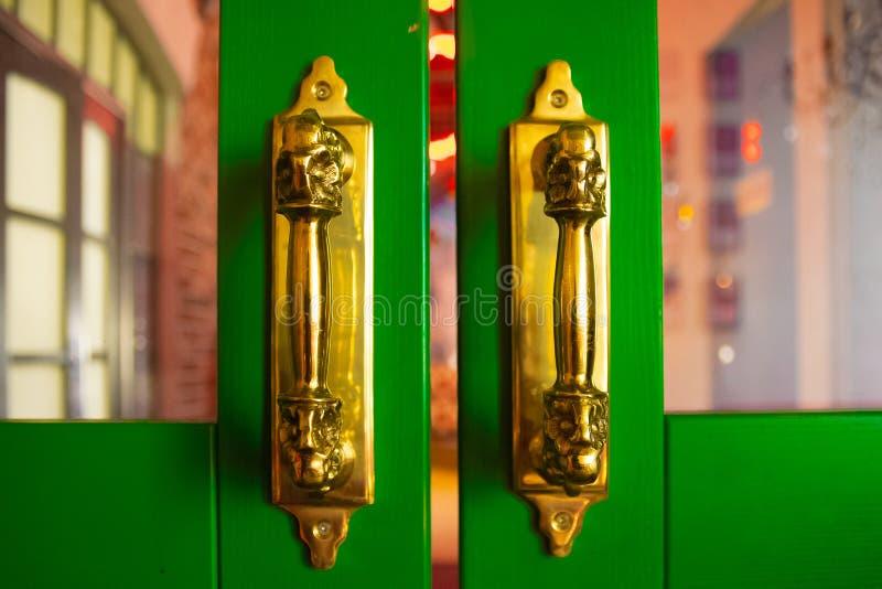 Puxadores da porta dourados na porta de madeira verde Fundo abstrato com espa?o imagens de stock