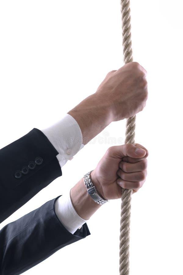 Puxar e ligação do homem de negócio amarrados com a corda concentrada fotografia de stock royalty free