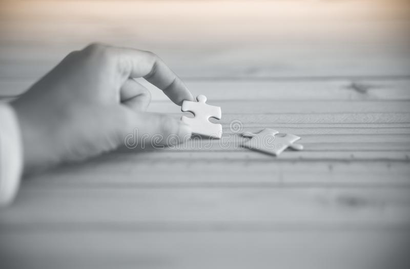 Puzzelholding met de hand op houten lijst royalty-vrije stock foto