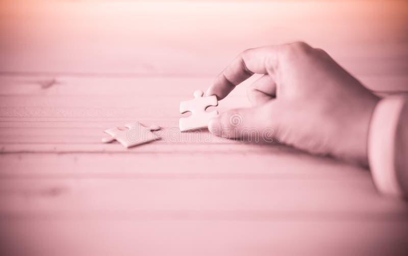 Puzzelholding met de hand op houten lijst stock foto