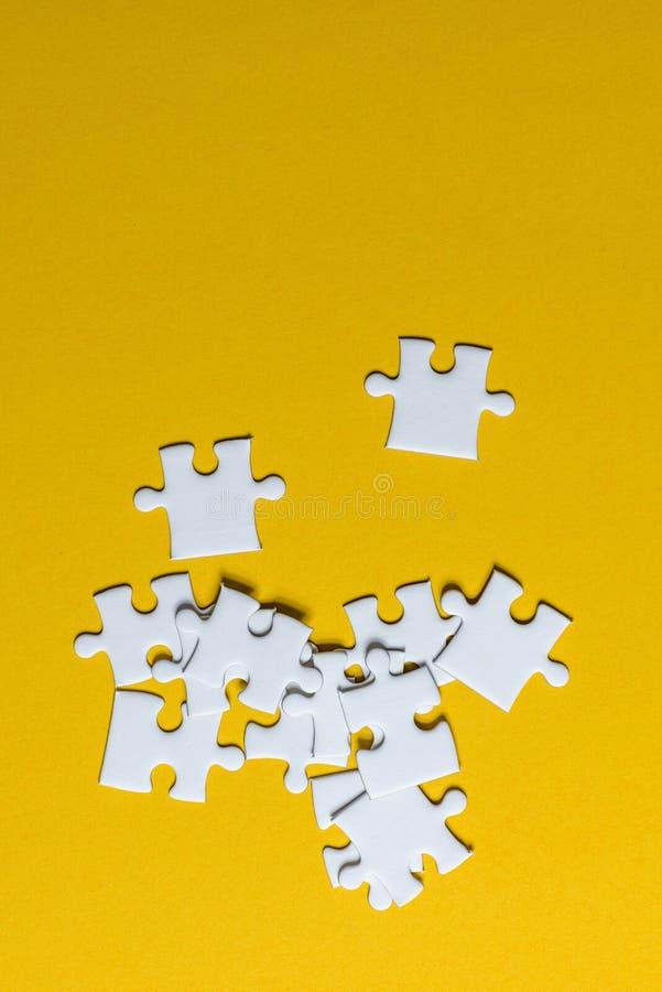 Puzzels op een geel Creatief concept als achtergrond met exemplaarruimte die worden geplaatst stock foto's