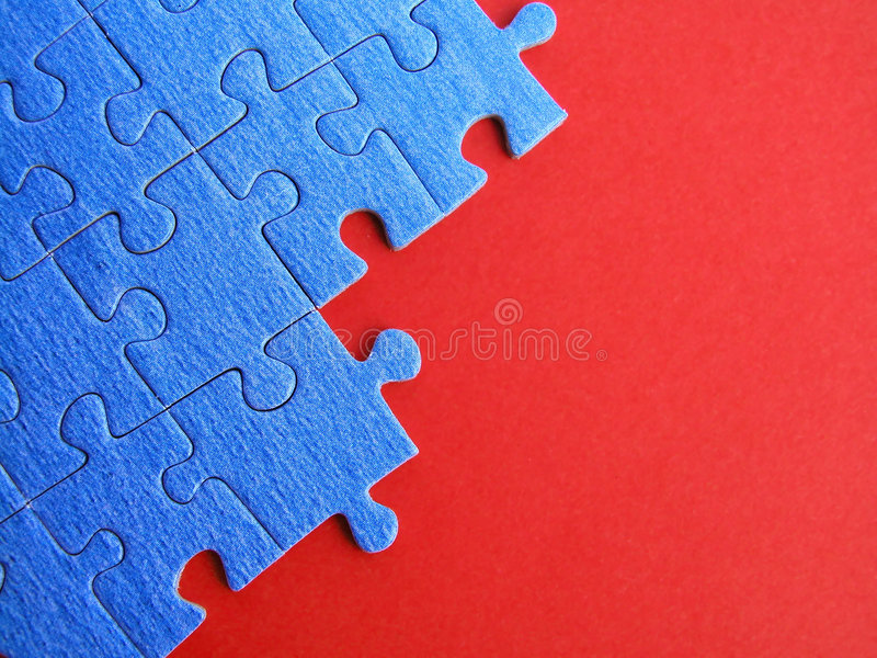 Puzzle. Blue puzzle on red stock photos