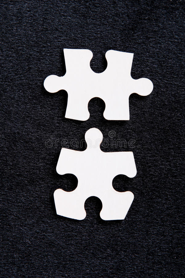 Puzzle. Two pieces of a puzzle on a black background stock photography