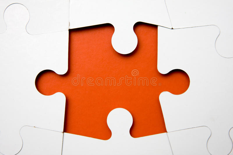 Puzzle. Missing puzzle piece - white on orange - metaphor for final step