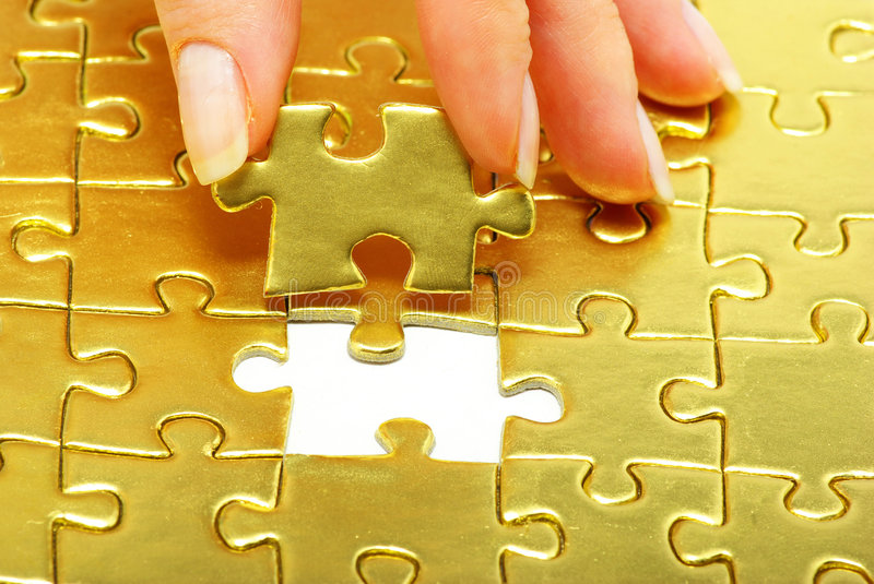 Puzzle. Woman fingers holdings gold pazles royalty free stock photo