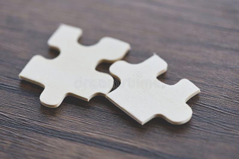 Puzzle auf Draufsicht des hölzernen Hintergrundes - zackige Verbindung des Stückes zwei stockfotos