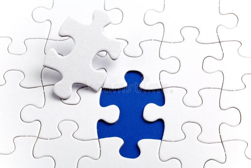 Puzzle bianco normale, su fondo blu fotografia stock libera da diritti