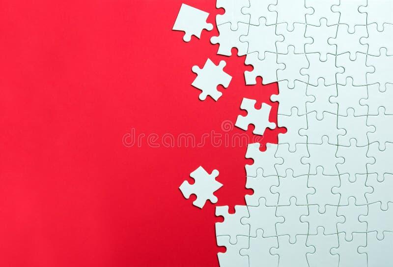 Puzzle bianco su fondo rosso immagine stock