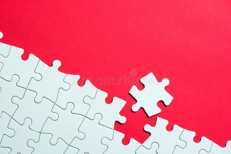 Puzzle bianco su fondo rosso fotografia stock libera da diritti