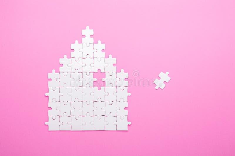 Puzzle blanc Puzzle de forme de Chambre Le concept du loyer, hypothèque Fond rose Vue supérieure photographie stock