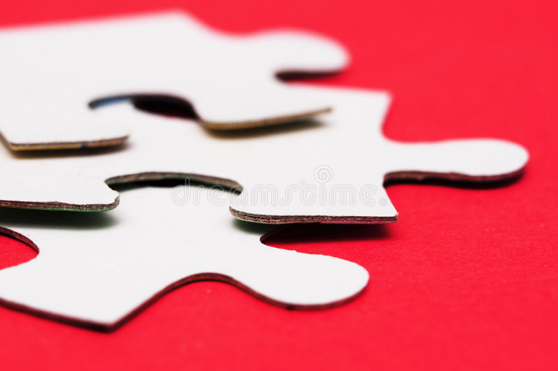 Puzzle blanc sur le rouge photos stock