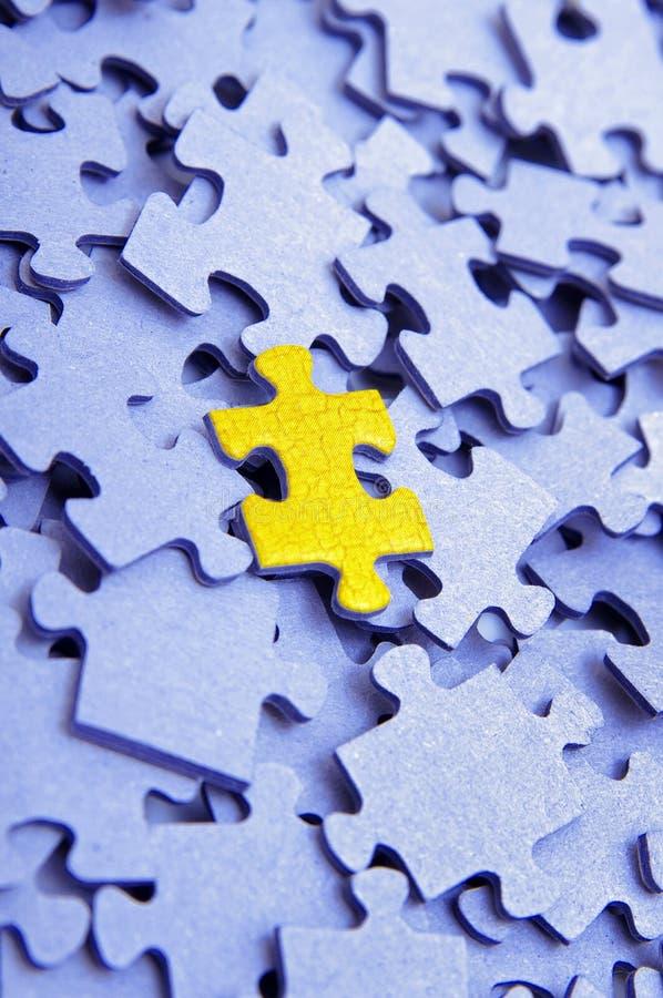 Puzzle blu con un elemento giallo immagini stock