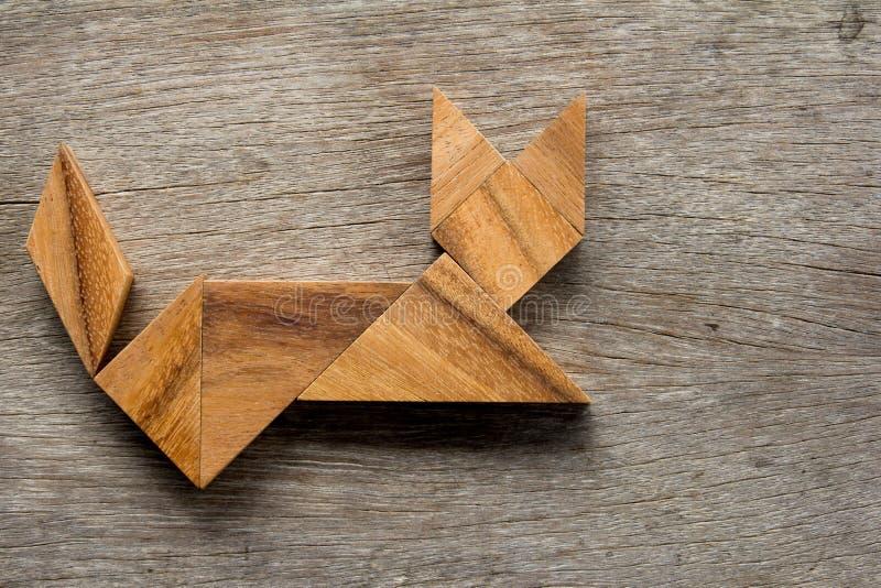 Puzzle cinese del tangram nella forma di seduta del gatto su fondo di legno fotografia stock