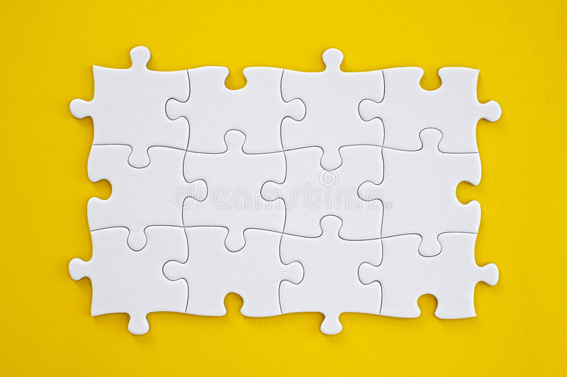 Puzzle. Connected blank puzzle pieces isolated on a yellow background royalty free stock image