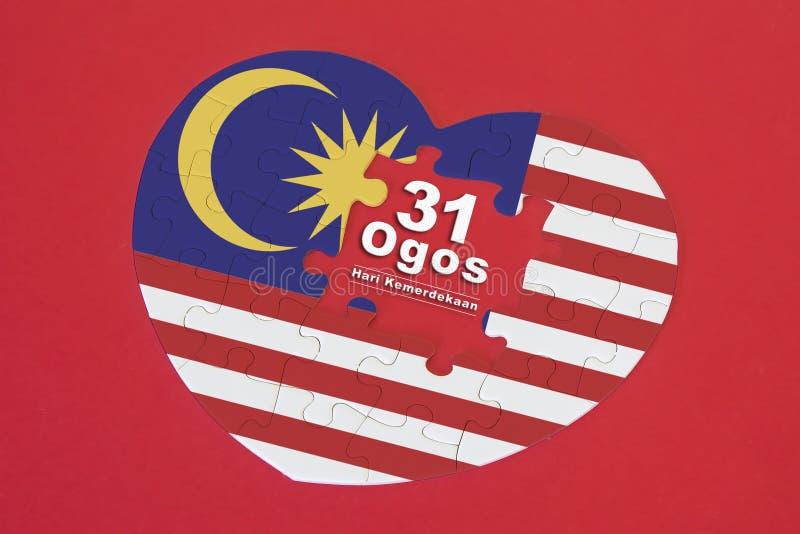 Puzzle denteux de drapeau de la Malaisie de forme de coeur avec un mot écrit 31 Ogos photo stock