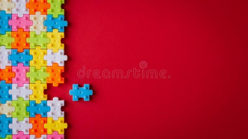 Puzzle denteux en plastique de couleurs sur le fond de papier rouge, manquant un puzzle denteux pour accomplir l'espace de copie photographie stock