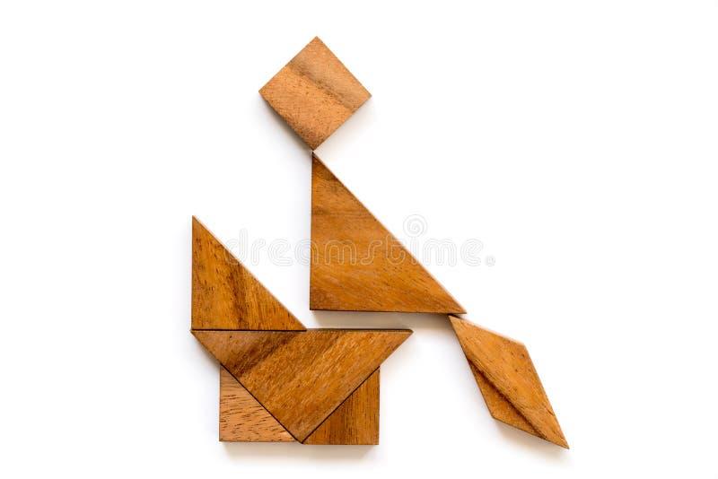 Puzzle di legno del tangram in uomo che si siede sulla sedia o sulla toilette nella forma della toilette su fondo bianco fotografia stock libera da diritti