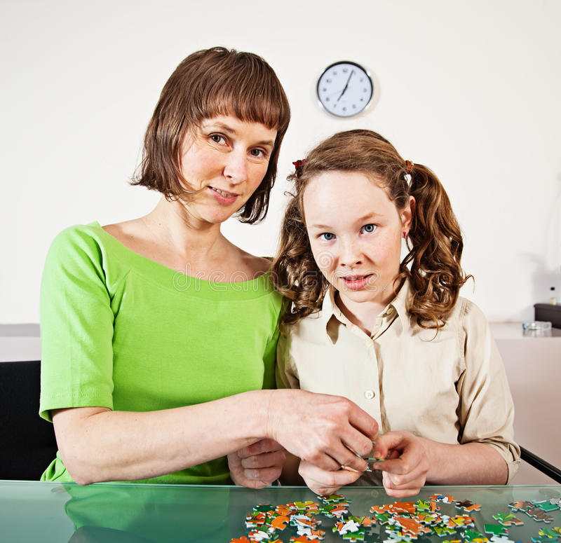 Puzzle di montaggio della ragazza dell'adolescente con la sua madre immagini stock